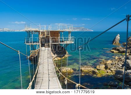 Place for relaxation with suspension foot-bridge on a Black Sea resort shore Crimea Ukraine.