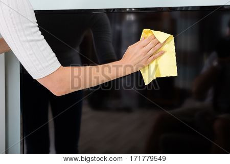 Close-up Of A Woman Hand Cleaning Television With Cloth At Home