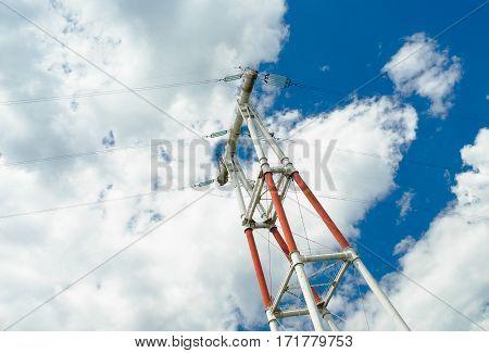 Electricity pylon against blue cloudy sky .