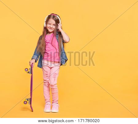 Cute little girl enjoying music using headphones and holding a skateboard over vivid yellow background with empty space. Full body studio portrait