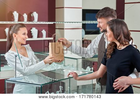 Receiving purchase. Attractive female jeweler smiling handing her customers paper shopping bag with purchased items buying consumerism couple love jewelry service profession occupation clients concept