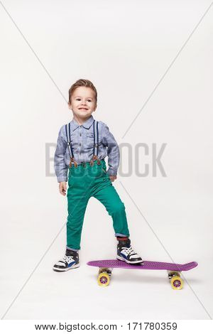 Full length Young skater kid boy isolated on white background. Little boy wearing stylish clothes standing on skateboard