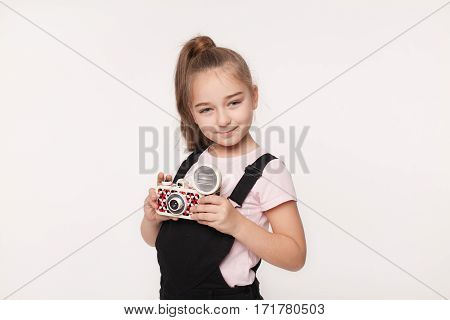 Teenage girl in casual clothing holding a instant camera isolated over white background.