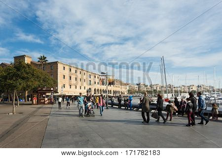 Barcelona Spain - January 08 2017: People are walking on the promenade near the History Museum of Catalonia at sunny day