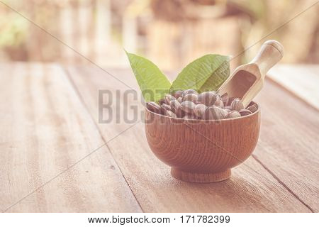 dried capsule seeds fruit of Sacha Inchi peanut in dish on wood