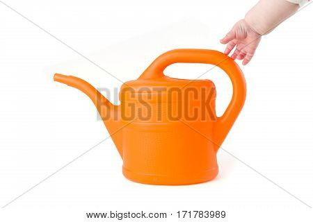Baby trying to grab orange watering can on white background studio shot