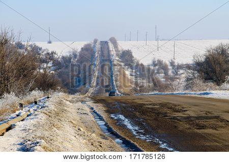 The broken cracked asphalt road on winter