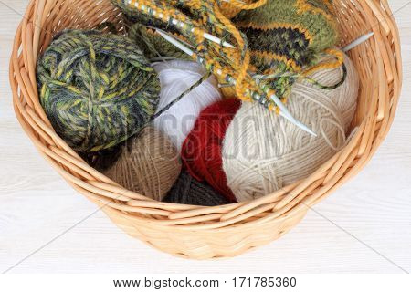 tangles of thread of different colors and knitting needles in a wicker basket / warming things from wool