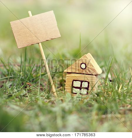 layout the little wooden house with a sign for the inscriptions on the background of grass / best offer ecological estate