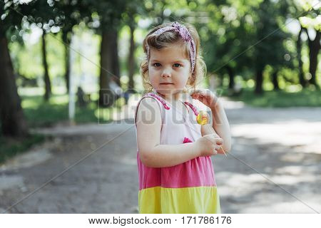 Funny child with candy lollipop, happy little girl eating big sugar lollipop, kid eat sweets.