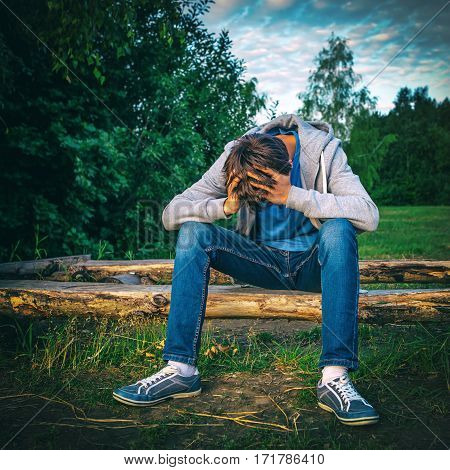 Vignetting Photo of Sad Teenager sit on the Log outdoor