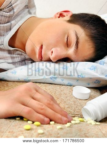 Teenager sleep near the scattered Pills on the Bed at the Home