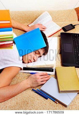 Tired Teenager sleep on the Sofa with the Books