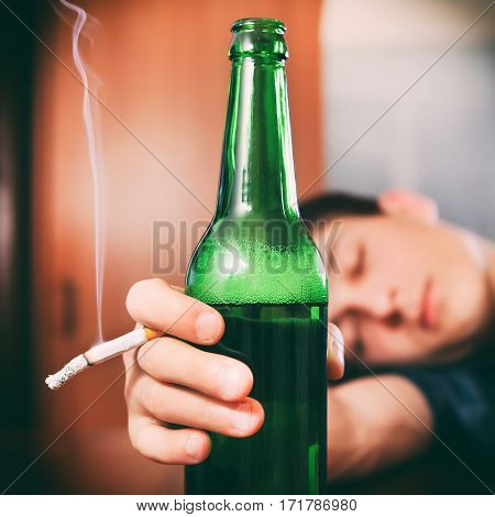 Toned Photo of Tired Young Man sleep with Bottle of the Beer and Cigarette