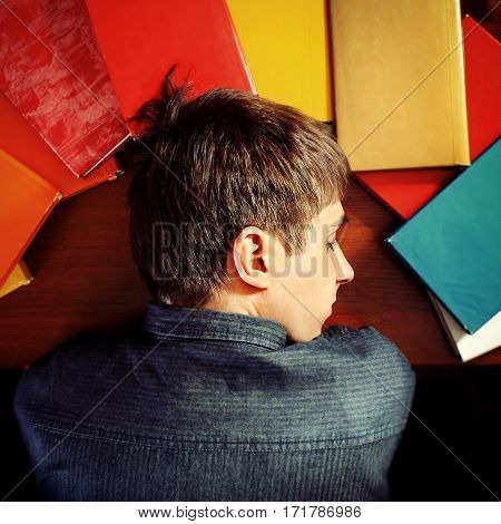 Toned Photo of Tired Teenager sleep on the Books at the Home