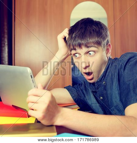 Toned Photo of Surprised Young Man with Tablet Computer at the Home