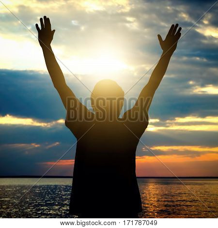 Toned Photo of Happy Man Silhouette with Hands Up on the Sunset Background