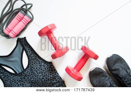 Flat lay of red dumbbell sport bra jump rope and sneakers sport equipments fitness items top view