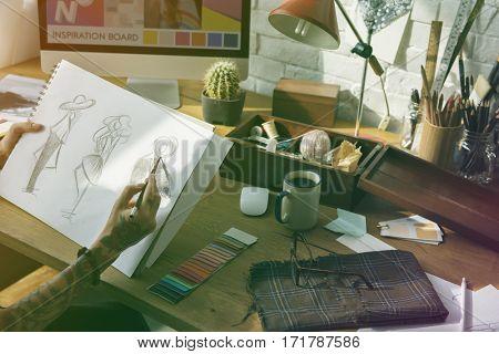 Fashion designer tattooed girl drawing cloth pattern