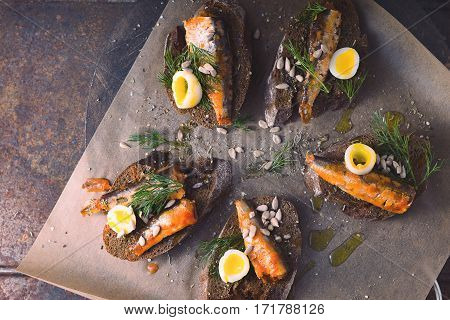 Sandwich. Rye bread and sardines on parchment horizontal