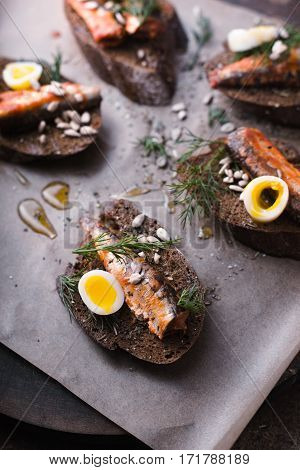 Sardines quail egg on rye bread top view vertical
