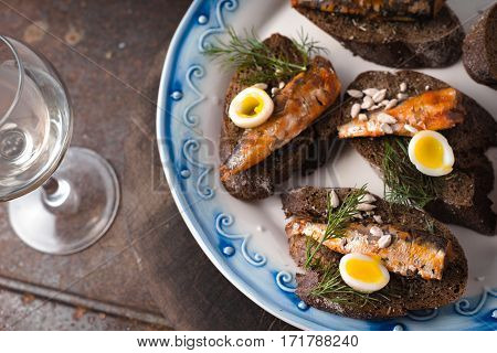 Sardines quail egg on rye bread on a ceramic plate and glass horizontal