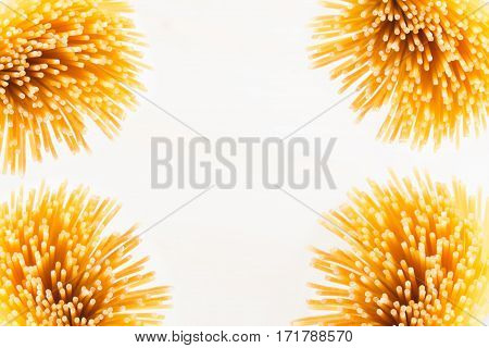 Decorative border of sheaf italian spaghetti with copy space top view on white background. Healthy food.