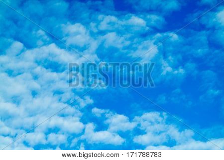 Blue sky background with white fluffy cumulus clouds