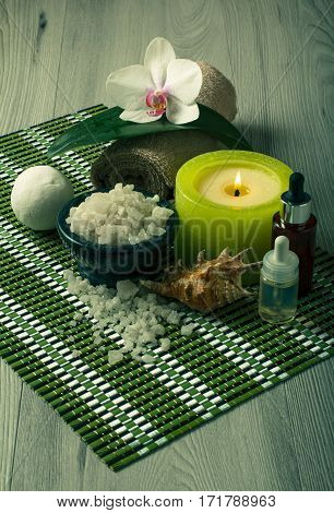 Spa and wellness setting with orchid flower bowl with sea salt bottles with aromatic oil seashell candle and towel on bamboo napkin