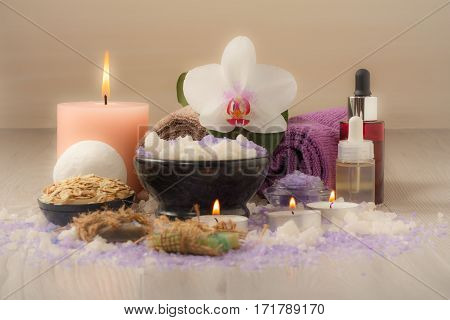 Spa composition with orchid flower bowl with sea salt bottles with aromatic oil soap scrub candles and towels on wooden board
