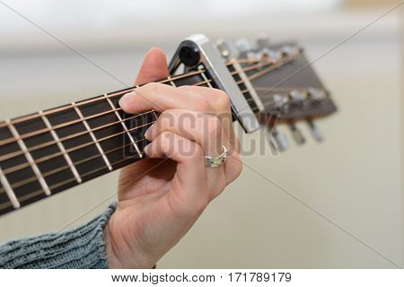 Person playing guitar with capo pod and grasping hand - detail