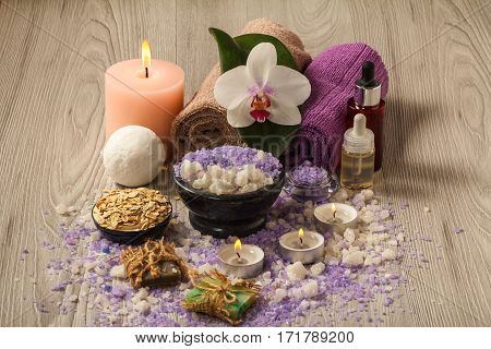 Spa accessories with orchid flower bowl with sea salt bottles with aromatic oil soap scrub candles and towels on wooden board