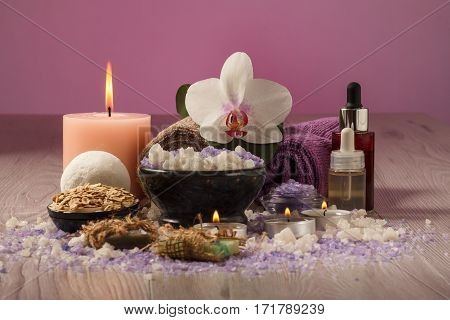 Spa composition with orchid flower bowl with sea salt bottles with aromatic oil soap scrub candles and towels on wooden board and pink background
