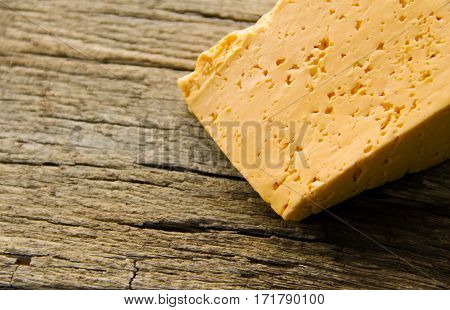 Piece of cheese on the wooden background