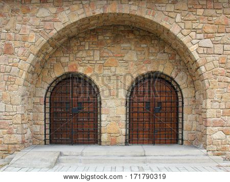 Double-arched stone temple entrance closed iron bars.