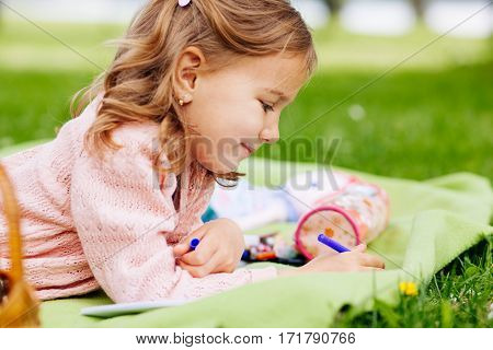 closeup of sweet little girl drawing in the park on the blanket