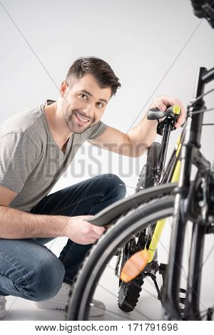 Young handsome man crouching while checking bicycle and smiling at camera