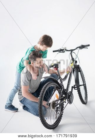 Happy father and son hugging while inspecting new bicycle on white