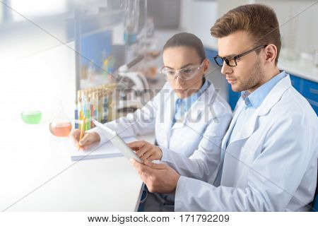 portrait of concentrated scientists using digital tablet during work in laboratory