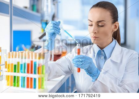 portrait of serious scientist working with laboratory tube