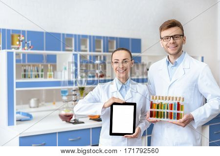 Young smiling chemists in lab coats holding digital tablet and test tubes