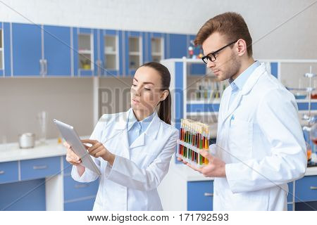 Young woman scientist showing digital tablet to colleague holding test tubes