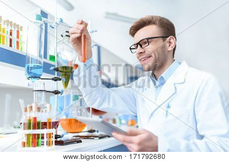 Young smiling man scientist holding digital tablet and looking at test tube in lab