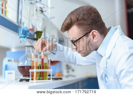 Side view of young man scientist holding test tube with reagent in lab