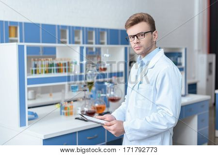Young man scientist in eyeglasses and lab coat holding digital tablet and looking at camera