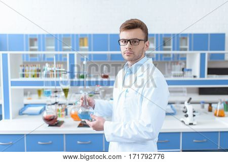 Young man scientist in eyeglasses holding flask with reagent and looking at camera