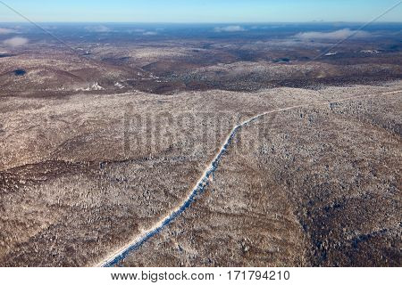 Aerial view of the oil pipeline running over a snow covered Ural Mountainous in winter.