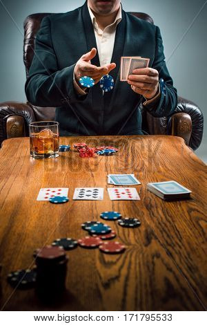 The man, chips for gamblings, drink and playing cards on wooden table. Poker concept