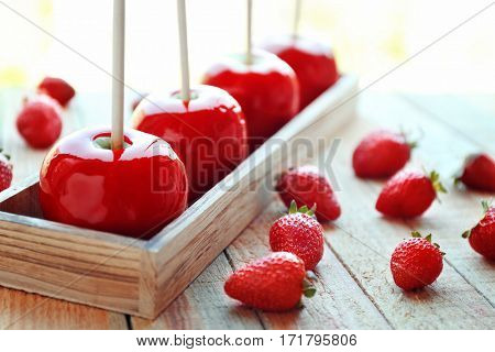 Candy apples with strawberry on wooden background