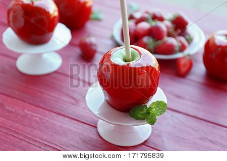 Candy apple on wooden table closeup
